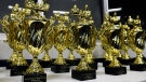 In this file photo, trophies are lined up at an event on Saturday, April 20, 2013 in Kalamazoo, Mich. A school in Wisconsin has announced that it will stop the handing out of cheerleading awards for female cheerleaders with the largest breasts and buttocks. (AP Photo/Kalamazoo Gazette-MLive Media Group, Matt Glade)