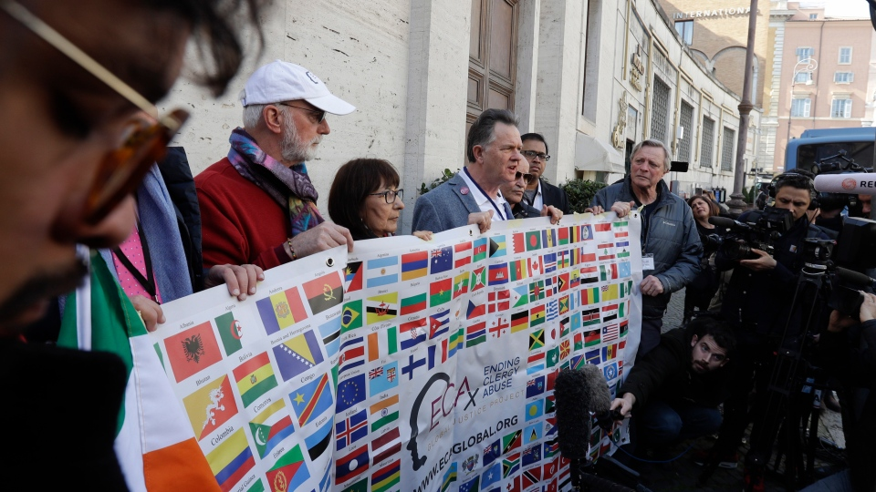 Sex abuse survivors and members of the ECA (Ending Clergy Abuse), including Canadian Evelyn Korkmaz, hold their organization banner as they talk to journalists at the Vatican, Wednesday, Feb. 20, 2019. (AP Photo/Gregorio Borgia)