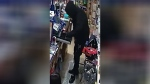 Surveillance image shows a man wearing all black emptying a cash register from a convenience store in Barrie, Ont. on Fri., Feb. 15, 2019 (Barrie Police Services)