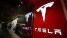 A sign bearing the company logo is displayed outside a Tesla store in Cherry Creek Mall in Denver, Feb. 9, 2019. (AP Photo/David Zalubowski, File)
