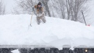 FILE PHOTO - Snow is removed from a roof (AP Photo/Mike Groll)