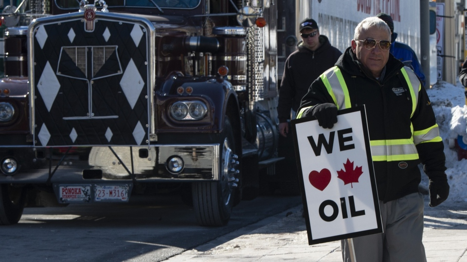 A pro-oil protester stands near convoy vehicles infront of Parliament Hill in Ottawa, Tuesday February 19, 2019. (THE CANADIAN PRESS/Adrian Wyld)