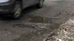 A vehicle is seen driving past a pothole on a downtown Toronto street on Feb. 20, 2019.