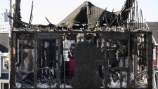 Police investigate through the charred remains of a fatal house fire in the Spryfield community in Halifax on Wednesday, February 20, 2019. (THE CANADIAN PRESS / Darren Calabrese)
