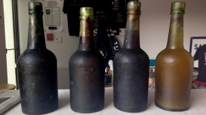 In this July 17, 2017 photo provided by Jamie Adams, four bottles recovered from the SS Oregon, a 133-year-old shipwreck, are shown at the Saint James Brewery in Holbrook, N.Y. (Jamie Adams via AP)
