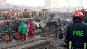 People gather to watch as firefighters damp down the area following a deadly fire in a poor residential area of the seaport city Chattogram, southern Bangladesh, Sunday Feb. 17, 2019. (AP Photo)