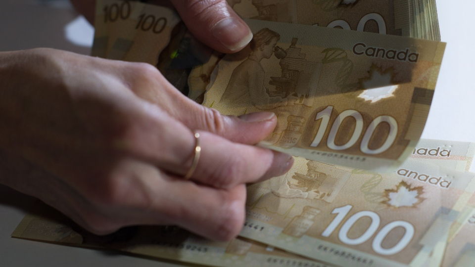 Canadian $100 bills are counted in Toronto, Feb. 2, 2016. (Graeme Roy/The Canadian Press)