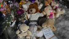 A memorial of flowers and stuffed animal toys is seen outside the scene of a fatal house fire in the Spryfield community in Halifax on Wednesday, February 20, 2019. The early-morning fire claimed the lives of seven Syrian refugee children and left the surviving mother and father in hospital. (THE CANADIAN PRESS/Darren Calabrese)