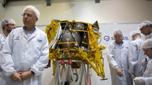 In this Monday, Dec. 17, 2018 file photo, technicians stand next to the SpaceX, lunar module, an unmanned spacecraft, on display in a special clean room during a press tour of their facility near Tel Aviv, Israel. (AP Photo/Ariel Schalit)