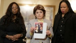 As Latresa Scaff, right, and Rochelle Washington, left, look on as attorney Gloria Allred holds up a picture of them as teenagers on the night they claim they became victims of musician R. Kelly's sexual advances during a news conference in New York, Thursday, Feb. 21, 2019. (AP Photo/Seth Wenig)