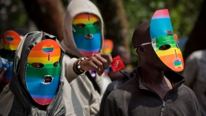 In this file photo of Monday Feb. 10, 2014, Kenyan people who identify as gay and lesbian and others supporting their cause, wear masks to preserve their anonymity and one holds out a wrapped condom, as they stage a rare protest in Nairobi, Kenya. (AP Photo/Ben Curtis-File)