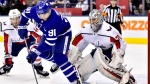 Toronto Maple Leafs centre John Tavares (91) tries to manage the puck in front of Washington Capitals goaltender Braden Holtby (70) as the Capitals' Brooks Orpik (44) looks on during second period NHL hockey action in Toronto on Thursday, Feb. 21, 2019. THE CANADIAN PRESS/Frank Gunn
