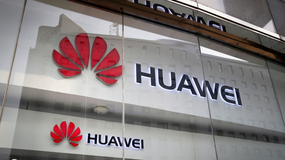 In this Jan. 29, 2019, file photo, the logos of Huawei are displayed at its retail shop window reflecting the Ministry of Foreign Affairs office in Beijing. (AP Photo/Andy Wong, File)