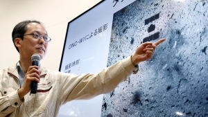 Associate Prof. Yuichi Tsuda of the Japan Aerospace Exploration Agency (JAXA) using an image of the surface of the asteroid Ryugu speaks about the touchdown by the Hayabusa2 spacecraft during a press conference in Sagamihara, near Tokyo, Friday, Feb. 22, 2019. (Kyodo News via AP)