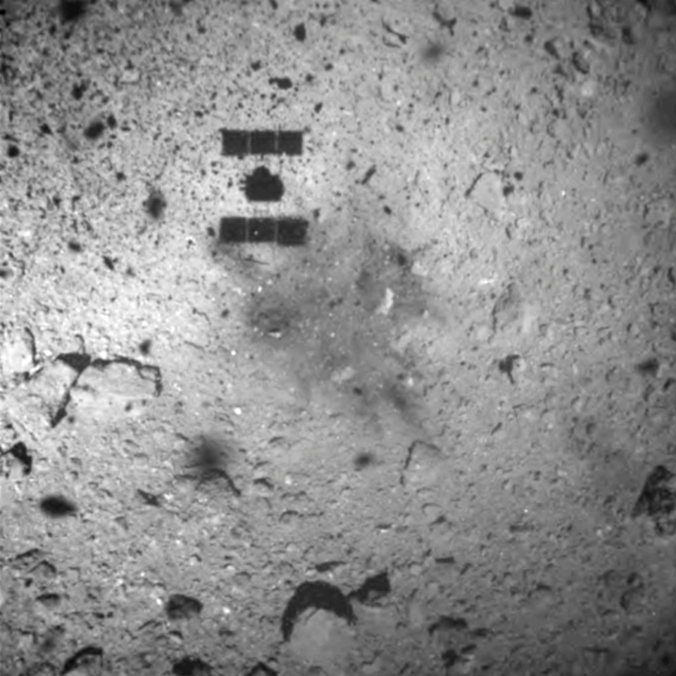 This image released by the Japan Aerospace Exploration Agency (JAXA) shows the shadow, center above, of the Hayabusa2 spacecraft after its successful touchdown on the asteroid Ryugu Friday, Feb. 22, 2019. (JAXA via AP)