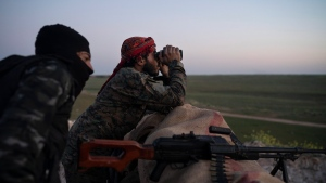 In this Tuesday, Feb. 19, 2019 file photo, U.S.-backed Syrian Democratic Forces fighters watch as an airstrike hits territory still held by Islamic State militants in the desert outside Baghouz, Syria. (AP Photo/Felipe Dana, File)