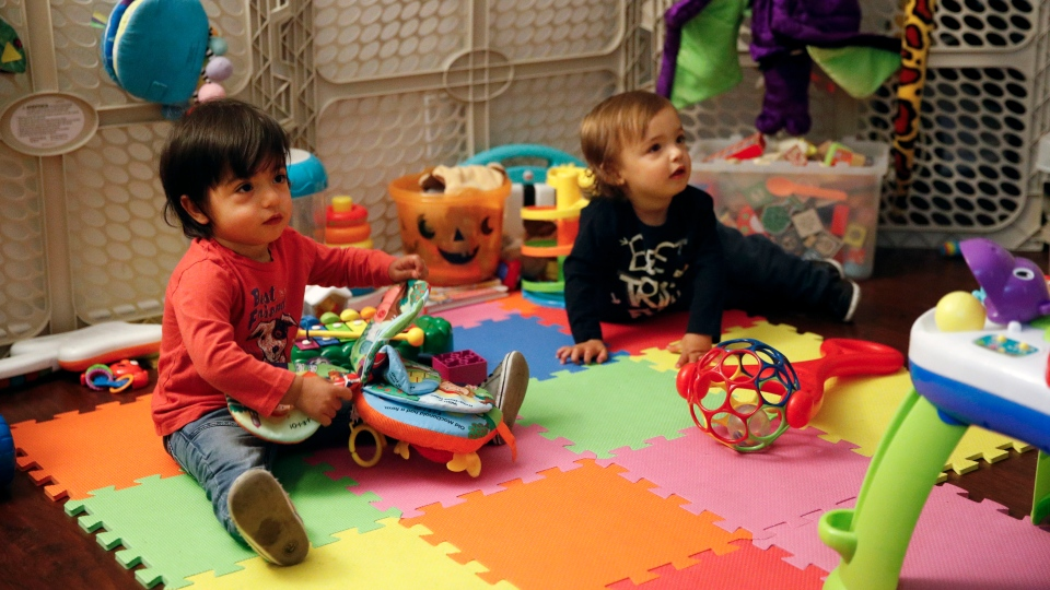 In this Jan. 23, 2018 file photo, sixteen-month-old Ethan Dvash-Banks, left, and his twin brother, Aiden, play in the living room of their apartment in Los Angeles. (AP Photo/Jae C. Hong, File)