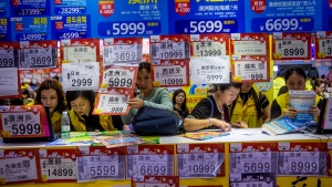 In this March 3, 2018, photo, people check on travel packages offered by travel agencies during the Guangzhou International Travel Fair in Guangzhou in south China's Guangdong province. (Chinatopix via AP)