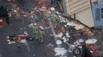In this Dec. 20, 2016 file photo firefighters look at the debris after the trailer has been towed away from the crime scene in Berlin, Germany, one the day after a truck ran into a crowded Christmas market and killed several people. (AP Photo/Markus Schreiber)