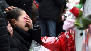 One of victim Vicente Juarez's daughter Diana Juarez cries at a makeshift memorial Sunday, Feb. 17, 2019, in Aurora, Ill., near Henry Pratt Co. manufacturing company where several were killed on Friday. (AP Photo/Nam Y. Huh)