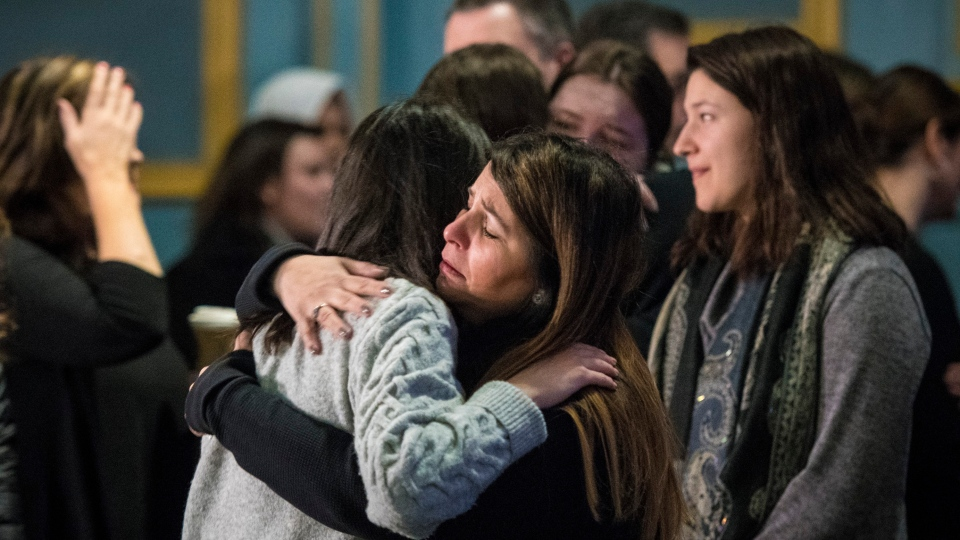 Survivors and loved ones affected by the shooting on Danforth Avenue in 2018, hug following their first public statement as a group at the Danforth Music Hall in Toronto on Friday, Feb. 22, 2019. (THE CANADIAN PRESS/ Tijana Martin)