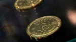 In this Dec. 8, 2017, file photo, coins are displayed next to a Bitcoin ATM in Hong Kong. (AP Photo/Kin Cheung, File)
