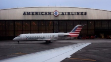 In this March 12, 2018, file photo, operations proceed outside the American Airlines facility at LaGuardia Airport in New York. (AP Photo/John Minchillo, File)