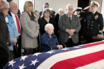 Rita Mendonsa, center, sits in front of her husband George's flag-draped casket during funeral services at St. Columba Cemetery in Middletown, R.I., Friday, Feb. 22, 2019. (AP Photo/Michael Dwyer)