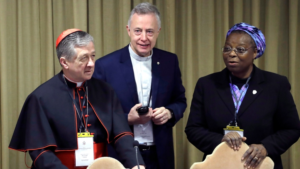 Sister Veronica Openibo, right, stands next to Chicago Archbishop Cardinal Blase J. Cupich, left, and Father Tomaz Mavric, center, as they wait for Pope Francis to arrive at the third day of a Vatican's conference on dealing with sex abuse by priests, at the Vatican, Saturday, Feb. 23, 2019. (AP Photo/Alessandra Tarantino, Pool)