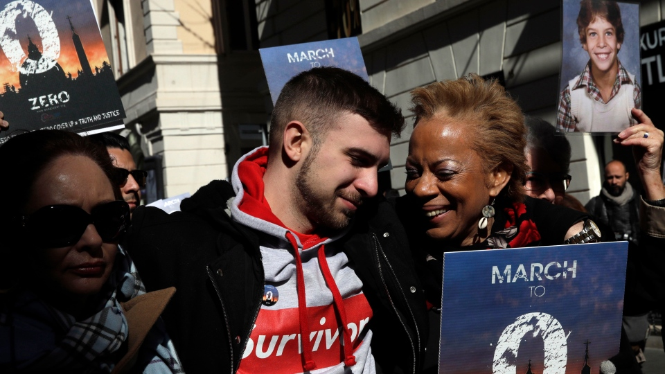 Sex abuse survivor Alessandro Battaglia is hugged by survivor and founding member of the ECA (Ending Clergy Abuse), Denise Buchanan, right, during a march in Rome, Saturday, Feb. 23, 2019. (AP Photo/Alessandra Tarantino)