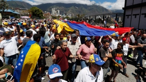 Opposition supporters converge in front of La Carlota military base urging soldiers to join their fight and allow the entry of U.S. humanitarian aid, in Caracas, Venezuela, Saturday, Feb. 23, 2019. Venezuela's military has served as the traditional arbiter of political disputes in the South American country, and in recent weeks, top leaders have pledged their unwavering loyalty to Maduro. However, many believe that lower-ranking troops who suffer from the same hardships as many other Venezuelans may be more inclined to now let the aid enter. (AP Photo/Eduardo Verdugo)