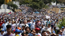 Opposition supporters march to La Carlota military base to urge soldiers to join their fight and allow the entry of U.S. humanitarian aid, in Caracas, Venezuela, Saturday, Feb. 23, 2019.