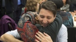 Prime Minister Justin Trudeau gets a hug as he visits caregivers and their family members at Malvern Family Resource Centre in Toronto on March 31, 2017. (THE CANADIAN PRESS/Frank Gunn)