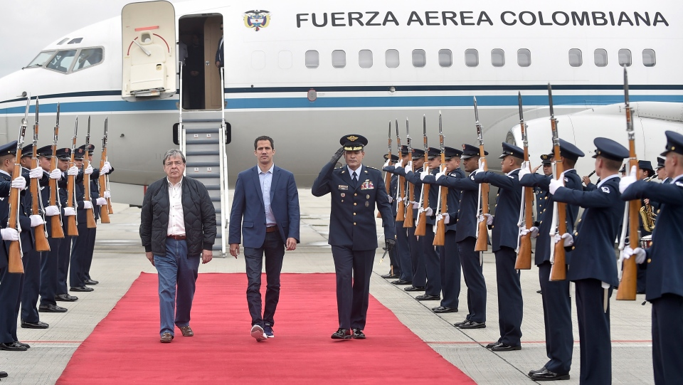In this photo released by Colombia's presidential press office, Venezuelan opposition leader Juan Guaido, who declared himself interim president of Venezuela, is escorted by Air Force Gen. Luis Carlos Cordoba, right, and Colombian Foreign Minister Carlos Holmes Trujillo during a welcome ceremony for him at the military airport in Bogota, Colombia, Sunday, Feb. 24, 2019.  (Efrain Herrera/Colombian presidential press office via AP)