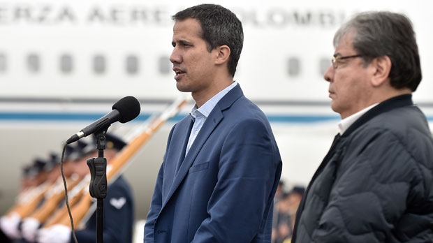 In this photo released by Colombia's presidential press office, Venezuelan opposition leader Juan Guaido, who declared himself interim president of Venezuela, makes a statement as Colombian Foreign Minister Carlos Holmes Trujillo stands by during a welcome ceremony for Guaido at the military airport in Bogota, Colombia, Sunday, Feb. 24, 2019. (Efrain Herrera/Colombian presidential press office via AP)