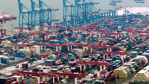 In this Feb. 14, 2019, photo, trucks move around containers stored at a port in Qingdao in east China's Shandong province. (Chinatopix via AP)