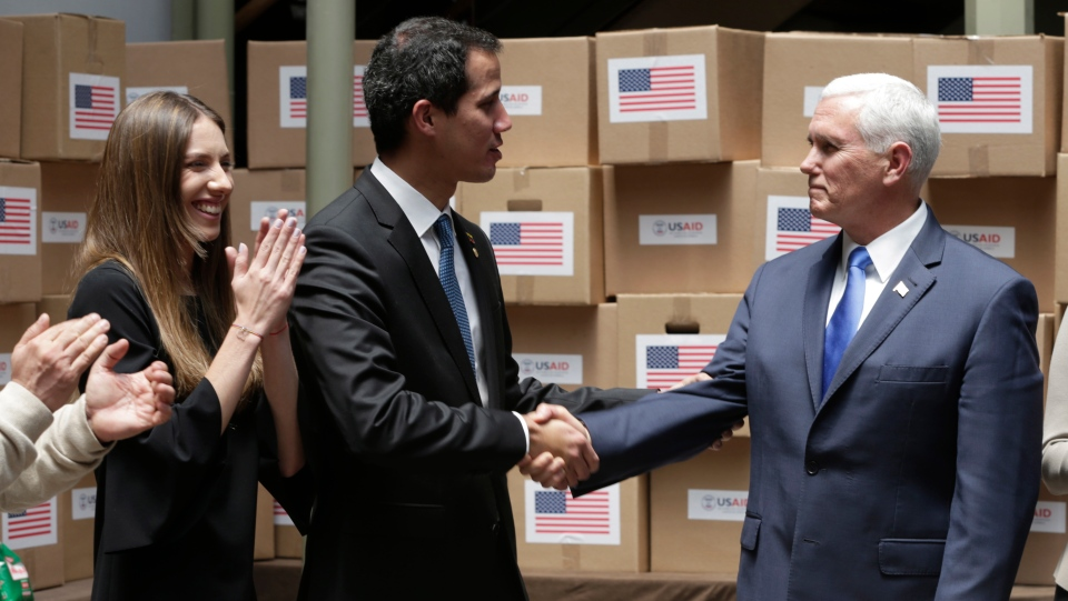 Venezuela's self-proclaimed interim president Juan Guaido, center, shakes hands with Vice President Mike Pence in a room filled with humanitarian aid destined for Venezuela where they met with a group of Venezuelan migrants, in Bogota, Colombia, Monday, Feb. 25, 2019. (AP Photo/Martin Mejia)