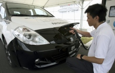 A Nissan Motor Co. staff recharges a super-quiet, zero-emission electric car that runs with a lithium-ion battery pack during a test-drive event at Nissan's facility in Yokosuka near Tokyo, Japan, Monday, July 27, 2009. (AP / Koji Sasahara)