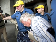 Unlicensed financial adviser Earl Jones is escorted out of the courthouse after being granted bail, in Montreal, on Tuesday, July 28, 2009. (Graham Hughes / THE CANADIAN PRESS)