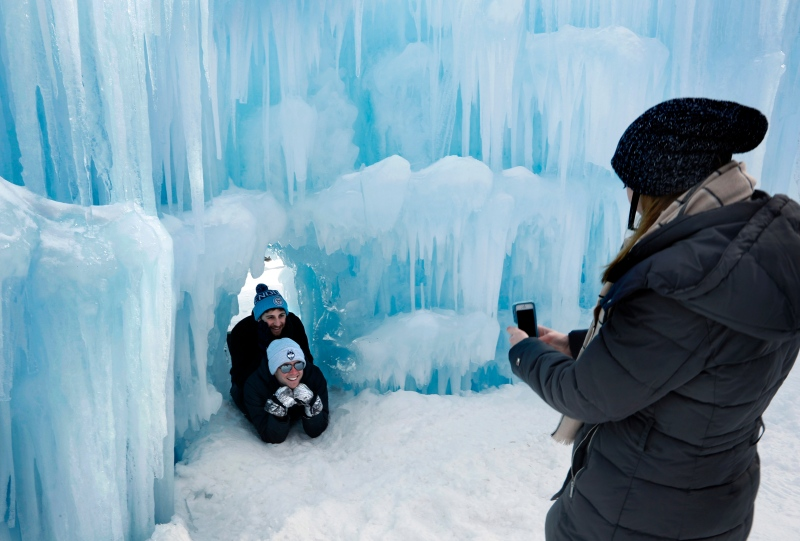 In this Saturday, Jan. 26, 2019 photo, visitors pose for a photo in a tunnel at Ice Castles in North Woodstock, N.H. With a seemingly endless variety of photo-ops, most visitors have a hard time putting their cameras down. (AP Photo/Robert F. Bukaty)