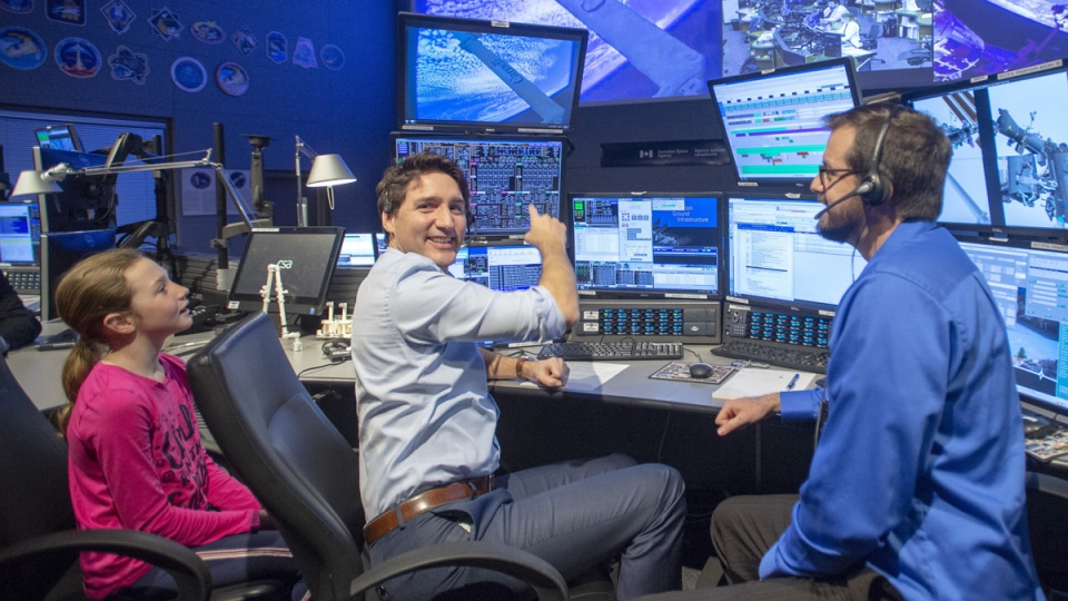 Prime Minister Justin Trudeau gets a look at the international space station's robotic control centre as his daughter, Ella-Grace, and robotic flight controller Jason Seagram look on at the Canadian Space Agency headquarters on February 28, 2019. (Ryan Remiorz / THE CANADIAN PRESS)