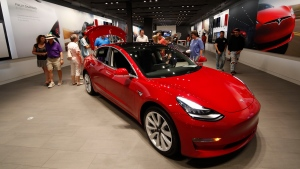 In this July 6, 2018, file photo, prospective customers confer with sales associates as a Model 3 sits on display in a Tesla showroom in the Cherry Creek Mall in Denver. (AP Photo/David Zalubowski)