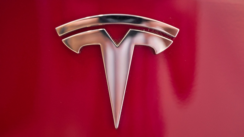 This Aug. 8, 2018, file photo shows a Tesla emblem on the back end of a Model S in the Tesla showroom in Santa Monica, Calif. (AP Photo/Richard Vogel, File)