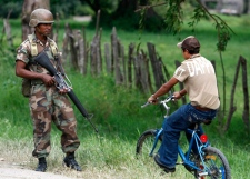 A boy rides a bicycle as a soldier stands guard in El Paraiso, Honduras' border with Nicaragua, Monday, July 27, 2009. (AP / Eduardo Verdugo)
