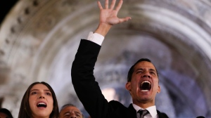 Accompanied by his wife Fabiana Rosales, Venezuela's self-proclaimed interim president Juan Guaido waves to supporters outside the Foreign Ministry in Buenos Aires, Argentina, Friday, March 1, 2019. (AP Photo/Natacha Pisarenko)