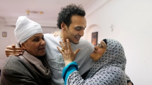 Mahmoud Abu Zaid, center, a photojournalist known as Shawkan, is hugged by his parents at his home in Cairo, Egypt, Monday, March 4, 2019. Shawkan was released after five years in prison. (AP Photo/Amr Nabil)