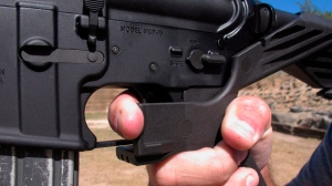 """In this Oct. 4, 2017 file photo, a shooting instructor demonstrates the grip on an AR-15 rifle fitted with a """"bump stock"""" at a gun club in North Carolina. (AP Photo/Allen G. Breed)"""