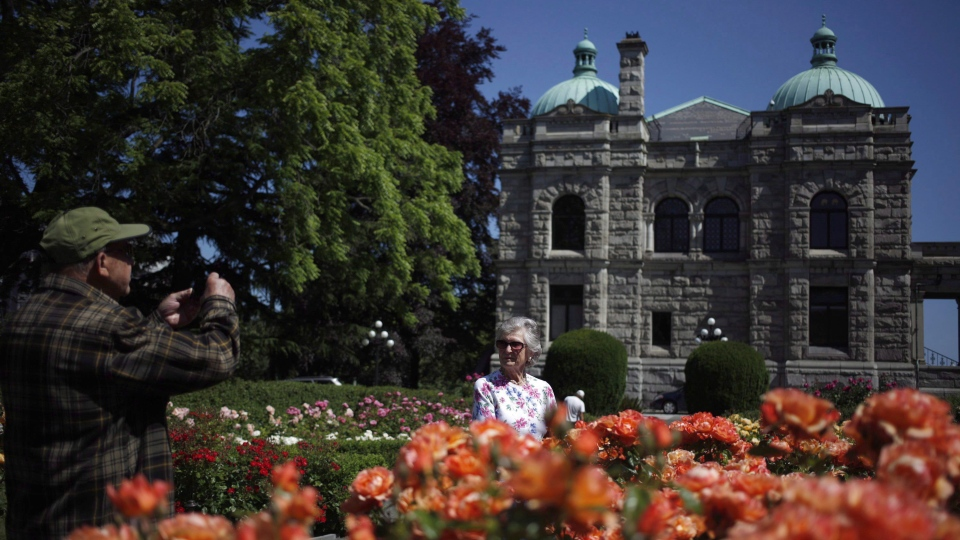 Tourists take pictures of flowers in the Rose Garden at the B.C. legislature in Victoria, B.C., on Thursday, June 29, 2017. (THE CANADIAN PRESS/Chad Hipolito)