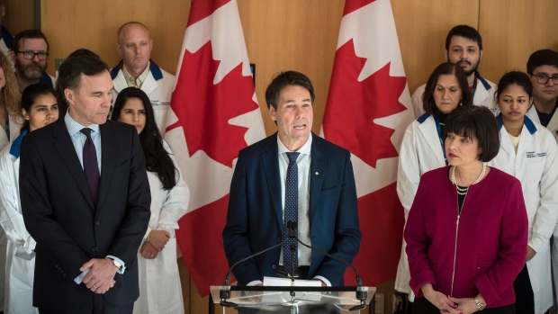 Bill Morneau, Minister of Finance, left to right, Dr. Eric Hoskins, Chair of the Advisory Council on the Implementation of National Pharmacare and Ginette Petitpas Taylor, federal Minister of Health, attend a press conference on the national pharmacare program at the Li Ka Shing Knowledge Institute in Toronto on Wednesday, March 6, 2019. THE CANADIAN PRESS/ Tijana Martin