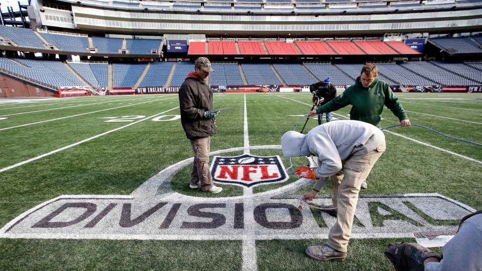 Gillette Stadium field crew apply paint to an NFL football AFC divisional round logo, Wednesday, Jan. 9, 2019, at Gillette Stadium in Foxborough, Mass. (AP Photo/Steven Senne)
